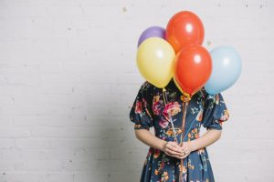 girl-holding-colorful-balloons-front-her-face-standing-against-wall_23-2148029658 (1)