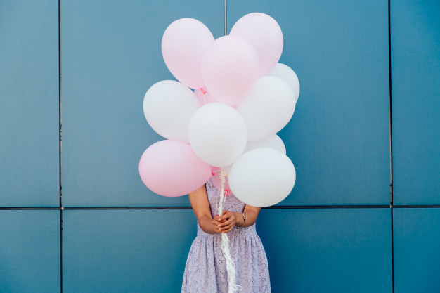 young-woman-hiding-her-face-with-bunch-balloons-standing-against-blue-wall_8353-6777