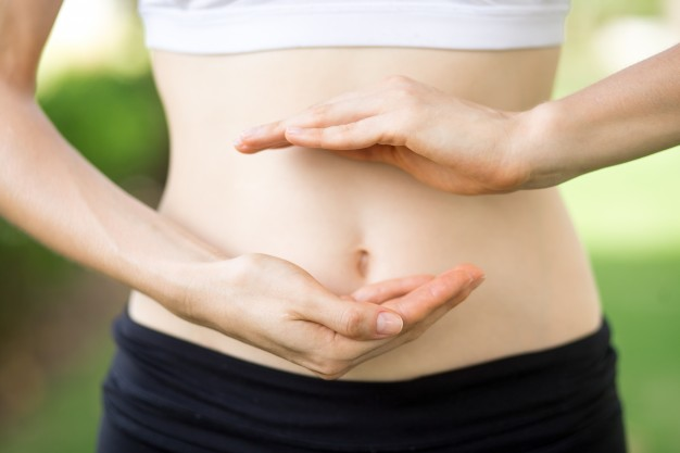 close-up-young-womans-hands-slim-belly_1262-3479