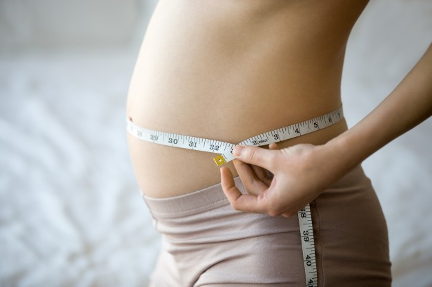 pregnant-woman-measuring-her-waist_1163-1529